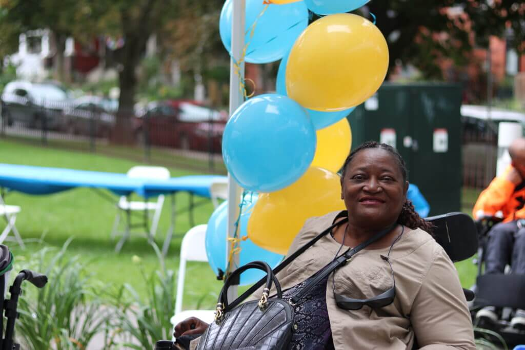 Bellwoods client in a wheelchair outdoors beside blue and yellow balloons